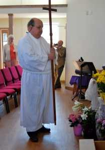 Board Member Chuck Young serves as crucifer for the procession